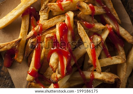Homemade French Fries Covered in Tomato Ketchup - stock photo