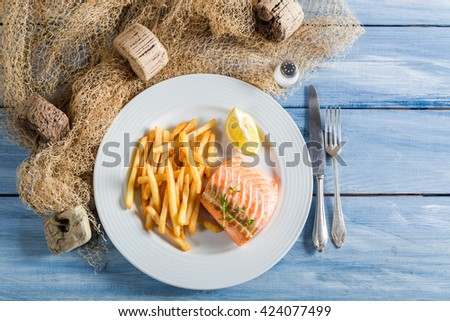 Homemade french fries with fresh salmon with lemon - stock photo