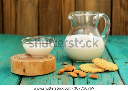 Homemade fresh almond milk in glass jar and glass bowl, with homemade almond cookies and whole almonds on shabby turquoise wooden table - stock photo