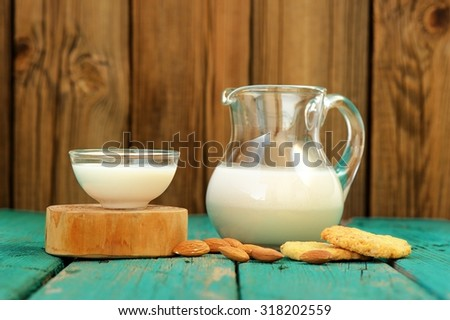 Homemade fresh almond milk in glass jar and glass bowl, with homemade almond cookies and whole almonds on shabby turquoise wooden table copyspace  horizontal - stock photo