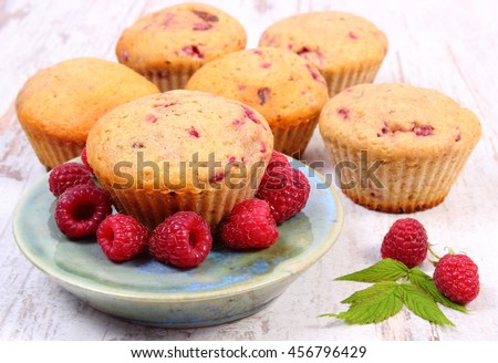 Homemade fresh baked muffins with raspberries on old rustic board, delicious dessert - stock photo