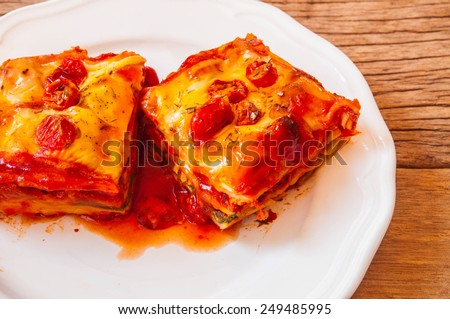 Homemade Fresh Lasagna topped with Melted Cheese and Tomato, Oven Baked, Italian Cuisine, Serve on Dish with tomato gravy sauce, wood table / Home Cooking Food Delicious. - stock photo