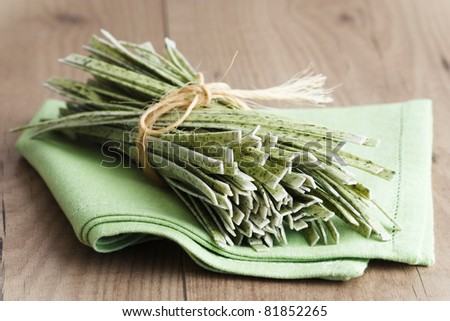 Homemade fresh pasta from wild garlic which is served on a green napkin and a wooden background.
