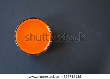 Homemade fresh-squeezed carrot juice  in glass on black wooden background.  View from top. - stock photo
