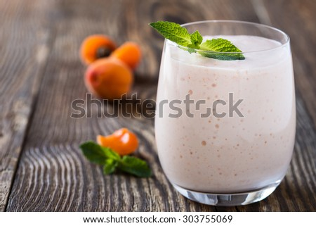 Homemade fresh summer fruits smoothie with ripe apricots on rustic wooden background - stock photo