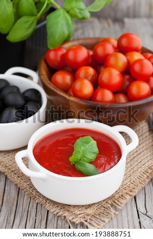 Homemade fresh tomato sauce and basil on old wooden background, selective focus - stock photo