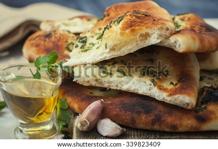 Homemade freshly baked flat bread and spices on a table. Selective focus - stock photo