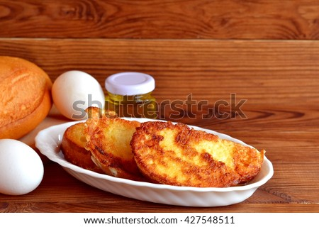 Homemade fried bread croutons. Fried bread with eggs for breakfast. Easy make roasted bread. Quick recipe. Ingredients for cooking snacks. Wooden background with blank space for text - stock photo