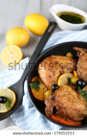 Homemade fried chicken drumsticks with vegetables on pan, on wooden background