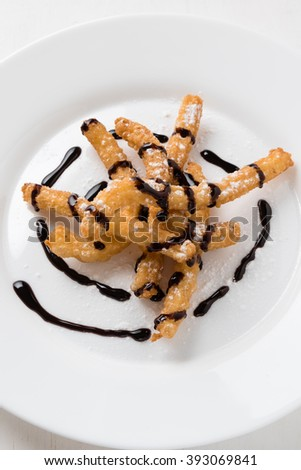 homemade fried churros dessert on white plate with chocolate