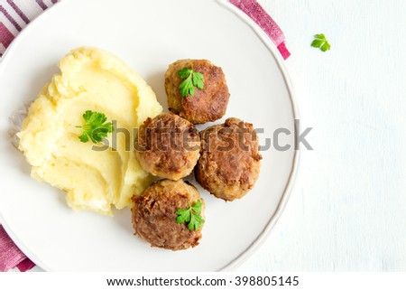 Homemade fried meatballs with mashed potatoes on white plate, copy space - stock photo
