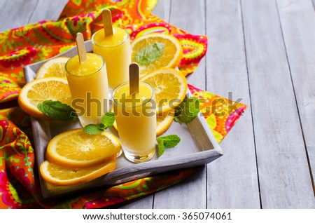 Homemade fruit popsicle with oranges and mint. Selective focus. - stock photo