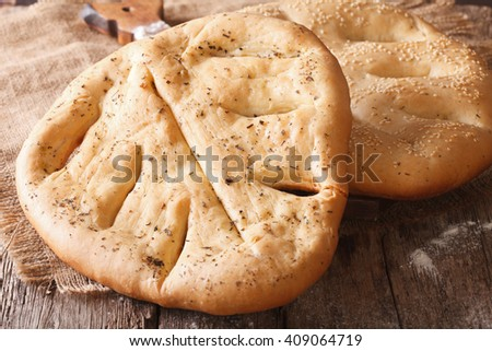 Fougasse French bread with sesame seeds and herbs closeup on the table ...
