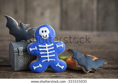 Homemade gingerbread cookies in the form as Halloween skeletons and bats on the wooden table. Space for text and selective focus. - stock photo