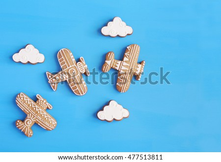 Homemade gingerbread cookies in the shape of airplanes and clouds on a blue table. Space for text and selective focus.