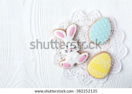 Homemade gingerbread cookies in the shape of the Easter bunny and painted eggs on a wooden table. Space for text and selective focus.