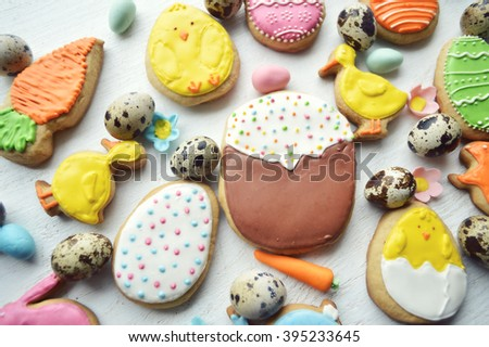 Homemade gingerbread cookies in the shape of the Easter bunny, painted eggs,chickens on a wooden table. Space for text and selective focus.Delicious Easter cookies background.