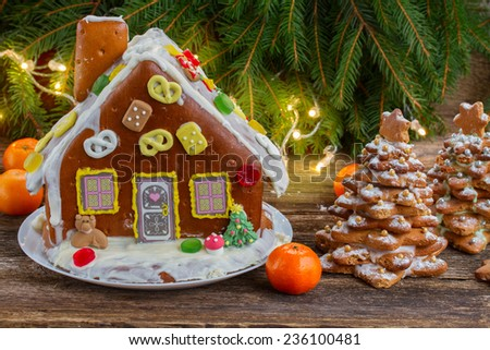 homemade gingerbread house with tangerines and  christmas lights on wooden table - stock photo
