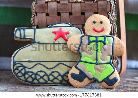 Homemade Gingerbread man in protective khaki uniforms and the tank on Defender of the Fatherland Day, selective focus on the man - stock photo