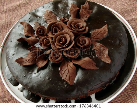 homemade glazed cake decorated with chocolate roses and leaves                             - stock photo