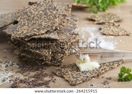 Homemade gluten free flax seed and sesame seed crispbread with butter and sea salt.