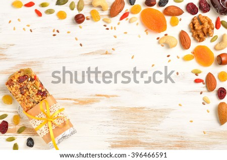 Homemade gluten free granola bars and mixed nuts, seeds, dried fruits on white wooden background. Copyspace background.Top view. - stock photo