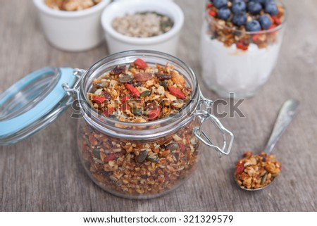 Homemade grain free granola made with mixed nuts, seeds, raisins with coconut yogurt on the back, selective focus - stock photo