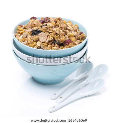 homemade granola in a bowl and spoons, isolated on white