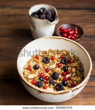 Homemade granola or muesli with oat flakes, corn flakes, dried fruits and toasted peanuts with fresh berries in a bowl, selective focus - stock photo