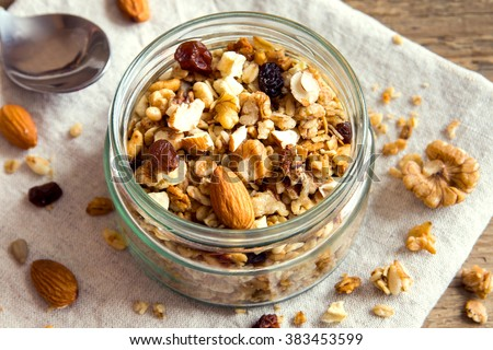 Homemade granola with nuts and seeds in glass jar for healthy breakfast - stock photo