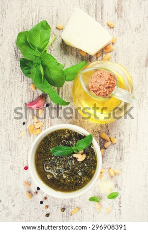 Homemade green basil pesto sauce and fresh ingredients. Italian Cuisine. Top view. Healthy food, diet and cooking concept. - stock photo