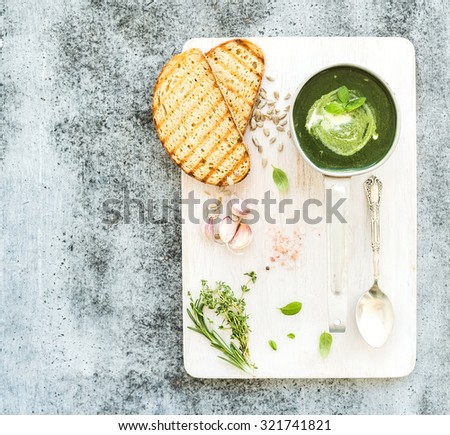 Homemade green spinach soup in a metal scoop with grilled bread slices, herbs, spices on white wooden  serving board over grunge grey background, top view, copy space - stock photo