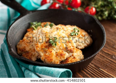 Homemade grilled chicken patties on a black skillet with tomatoes and fresh thyme on rustic wooden table - stock photo