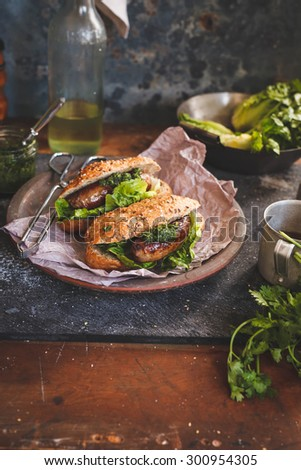Homemade grilled sausages sandwich with leaves of salad and whole grain mini baguette over on vintage ceramic plate from above on stone dark table with bottle of wine.  Rustic vertical image. - stock photo