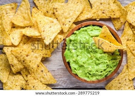 homemade guacamole with corn chips top view on rustic wooden table - stock photo