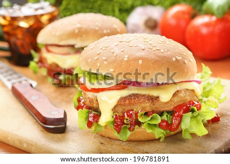 Homemade hamburger with fresh vegetables on wooden cutting board - stock photo