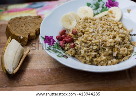 homemade healthy Breakfast of porridge with banana and brown bread - stock photo