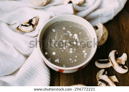 homemade healthy vegetarian champignon mushroom cream soup in the ceramic bowl on the dark wooden and white fabric background in rustic style natural light overhead shot  - stock photo
