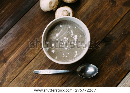 homemade healthy vegetarian champignon mushroom cream soup in the ceramic bowl on the dark wooden background in rustic style natural light overhead shot  - stock photo