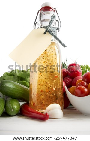 Homemade herb dressing in bottle and salad ingredients - stock photo