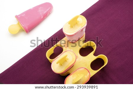 Homemade ice cream pops on white and purple background - stock photo