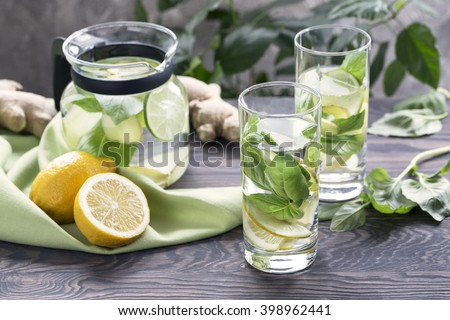 Homemade infused water with lemon, basil and ginger in transparent glasses and jug - stock photo