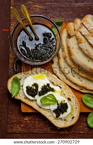 homemade Italian bread with mozzarella and basil pesto. village style - stock photo