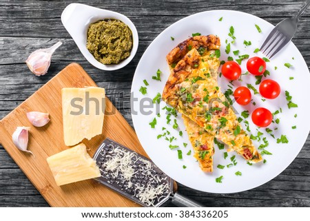 Homemade Italian terrific omelette frittata with eggs, ricotta, onion, tomatoes and bell peppers on a white dish, pieces of parmesan cheese and grater on an old wooden table, top view - stock photo