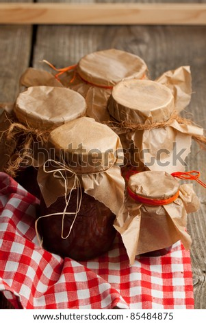 Homemade jam in glass jars on old wooden table - stock photo