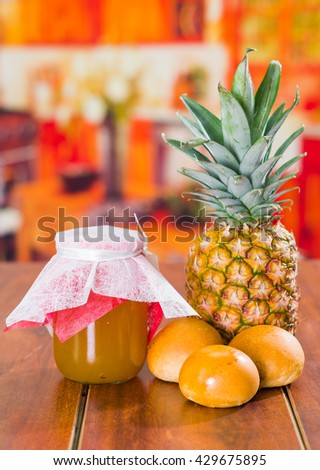 Homemade jam of pineapple with fresh fruit and little bread on a wooden table - stock photo