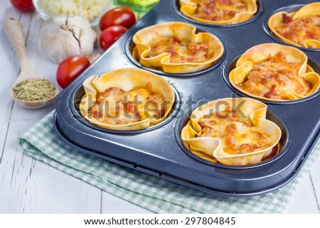 Homemade lasagna cups with minced meat, bolognese sauce topped with cheese - stock photo