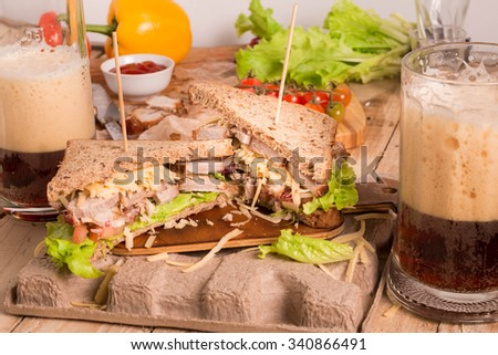 Homemade Leftover Thanksgiving Dinner Sandwich with Roast Meat, Cheese and Vegetables. Sandwich with Roast Meat Served with Mug of Beer. Dark Beer. - stock photo