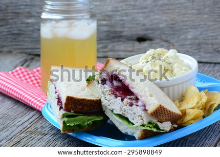 Homemade Leftover Thanksgiving Dinner Turkey Sandwich with Cranberries on Wood - stock photo