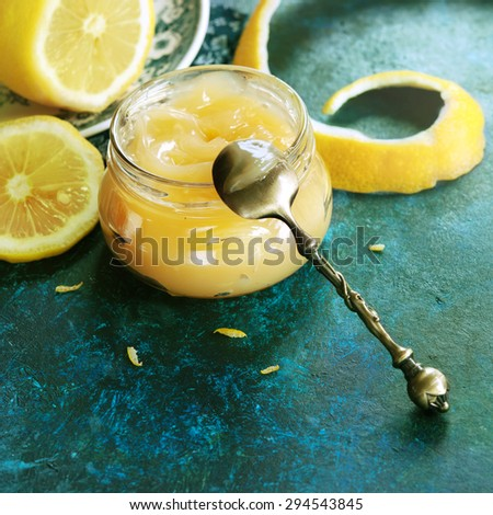 Homemade lemon curd in glass jar, with fresh lemons (toned picture) - stock photo